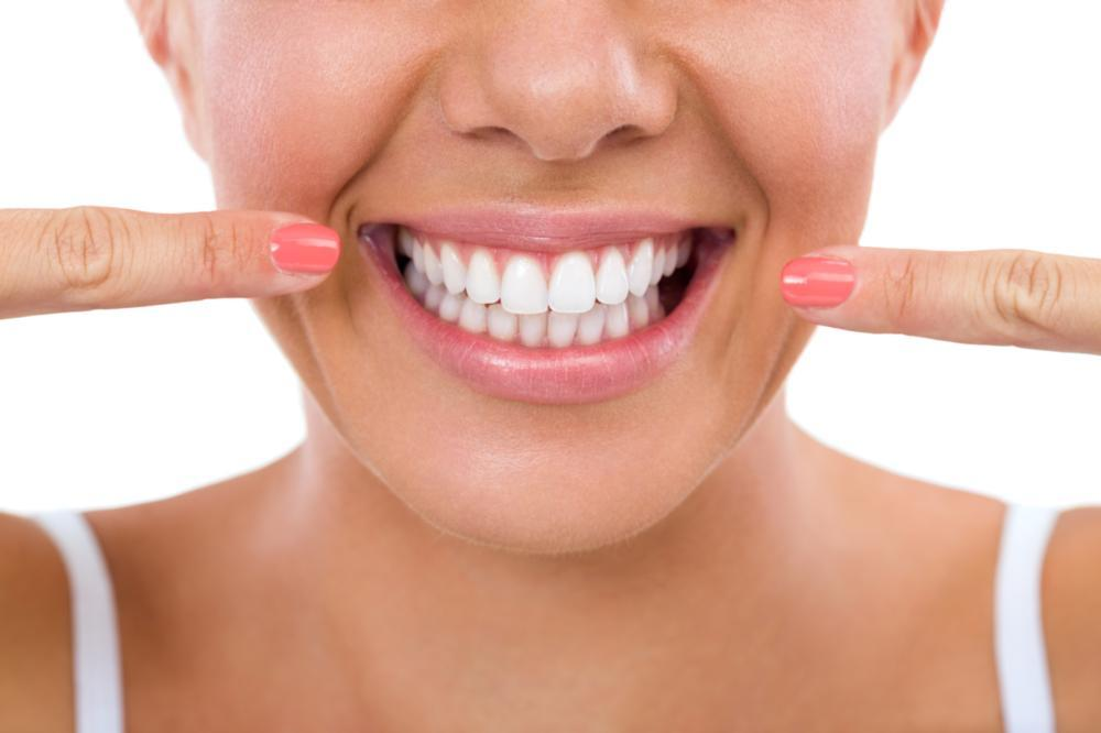 woman pointing at her teeth | teeth whitening Elk Grove Village, IL