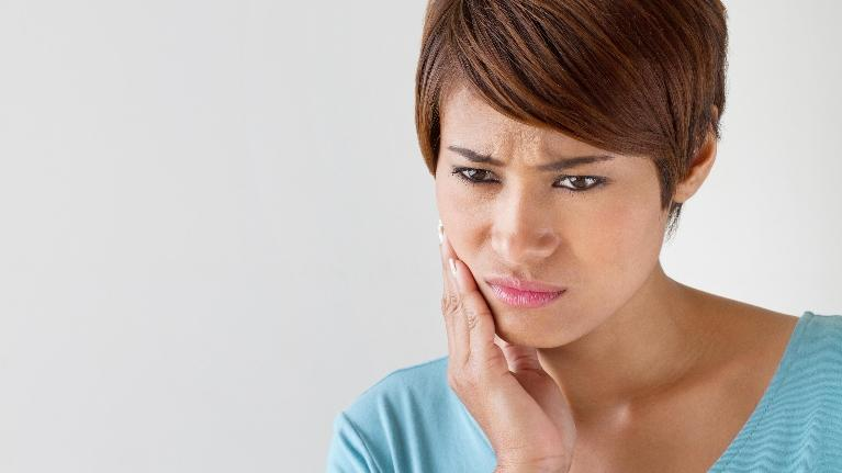 woman holding her mouth in pain | wisdom teeth extraction elk grove village
